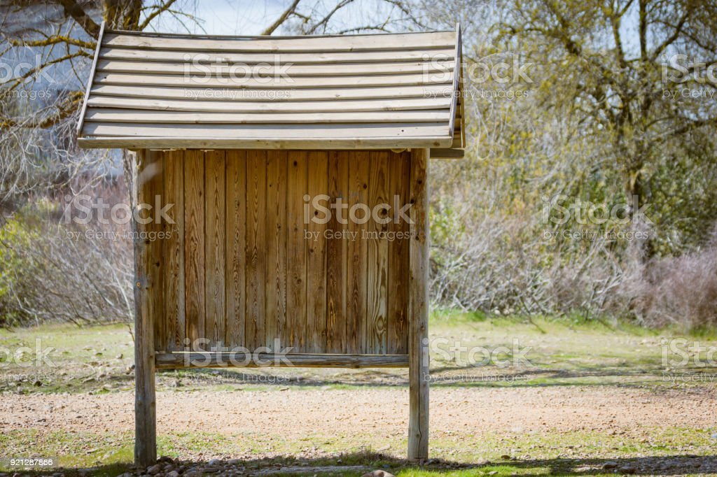 Brown wooden sign post with roof like house for information banner stock photo