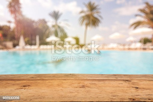 Brown Wooden Table and Blurred Swimming Pool