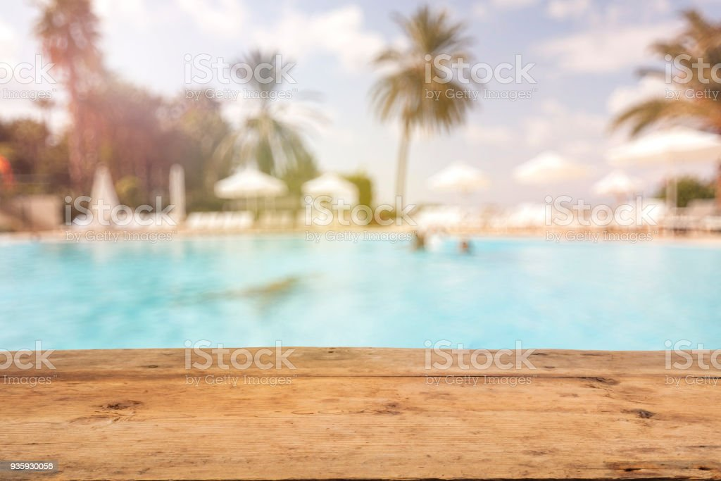 Brown Wooden Table and Blurred Swimming Pool stock photo