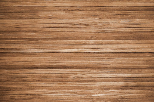 Directly above view of dark brown wooden background. This background features a wood grain pattern complete with nearly straight lines. The color of the wood appears darker near the left and right, but becomes lighter in the middle.