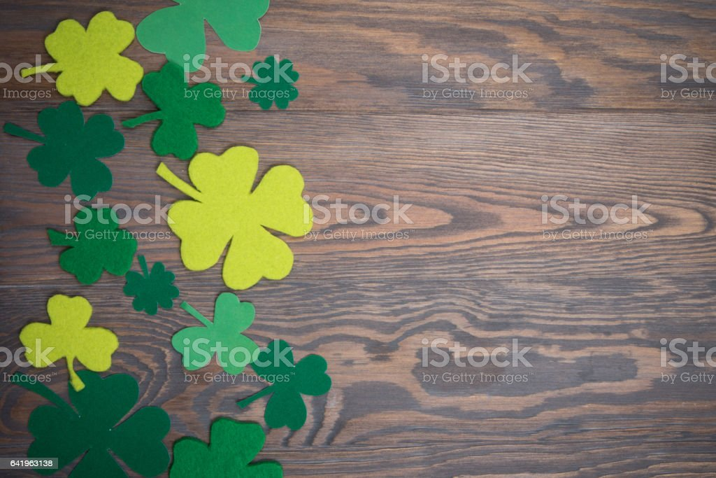 Brown wooden table with handmade green leaves of clover stock photo