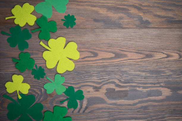 brown wooden table with handmade green leaves of clover - st patricks days stock photos and pictures