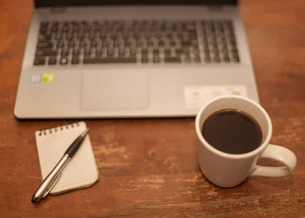 braun holztisch mit laptop notizblock stift und eine tasse schwarzen kaffee in einer erholsamen pause zeit szene - schwarzer kaffee net stock-fotos und bilder