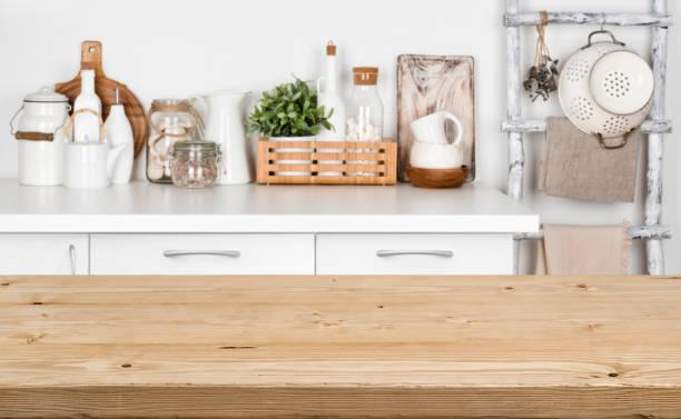 braune hölzerne struktur tabelle über verschwommenes bild der küchenbank - küche deko grün stock-fotos und bilder