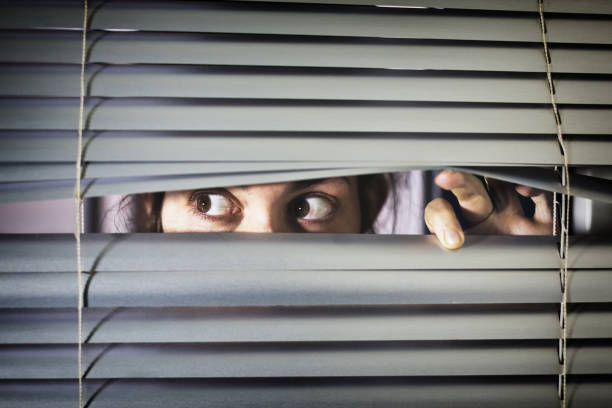 Brown-eyed girl peeps fearfully through venetian blinds A young woman with brown eyes looks sideways nervous through closed blinds. stealth stock pictures, royalty-free photos & images