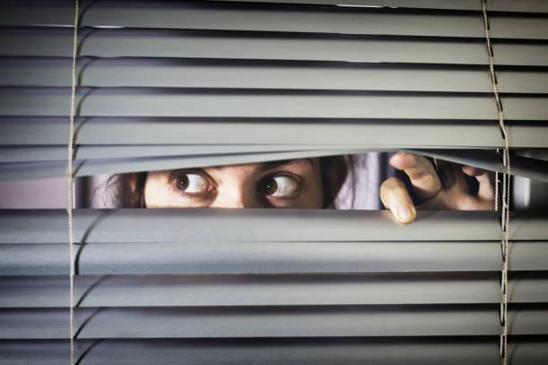 Brown-eyed girl peeps fearfully through venetian blinds stock photo