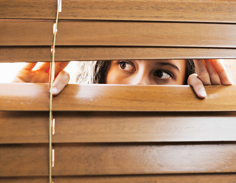 Young woman peers out of a window.