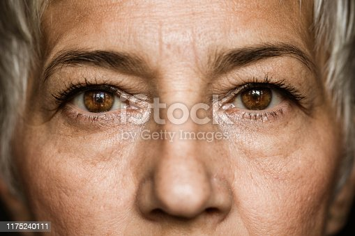 Close up of senior woman's brown eyes looking at camera.