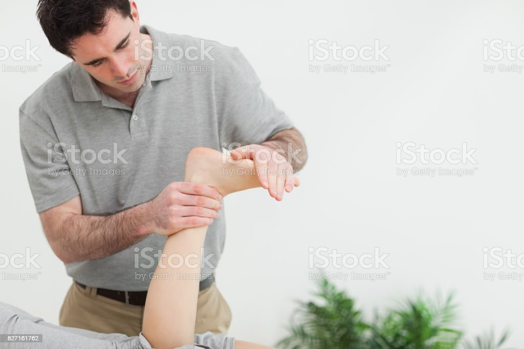 Brownhaired therapist stretching the foot of a patient stock photo