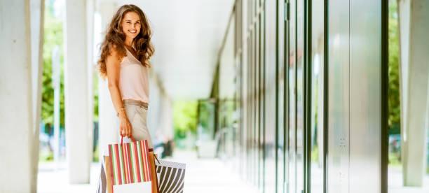 Braunhaarige Frau lächelnd halten bunte Einkaufstaschen – Foto