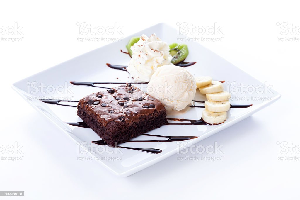 Brownie and ice cream with whipping cream and banana stock photo
