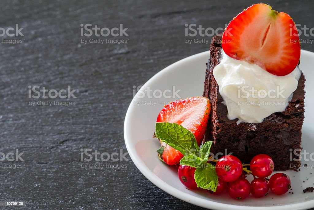 Brownie with nuts, chocolate, mint, stawberry, dark stone background stock photo