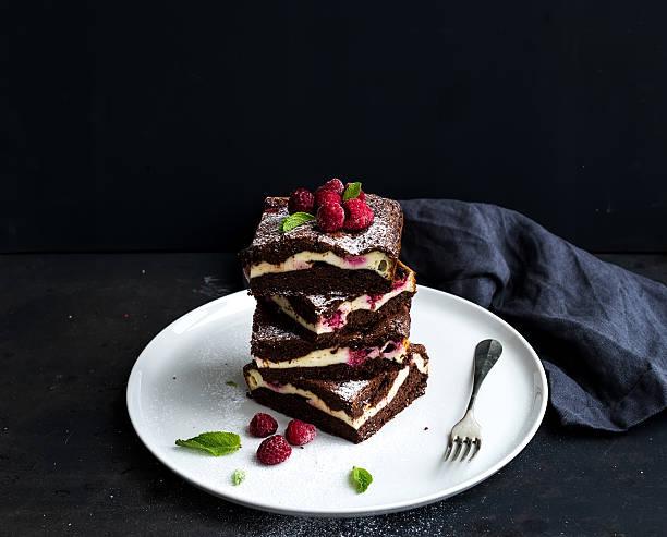 brownie-käsekuchen tower mit himbeeren auf weißem teller, schwarzer hintergrund - cupcake türme stock-fotos und bilder