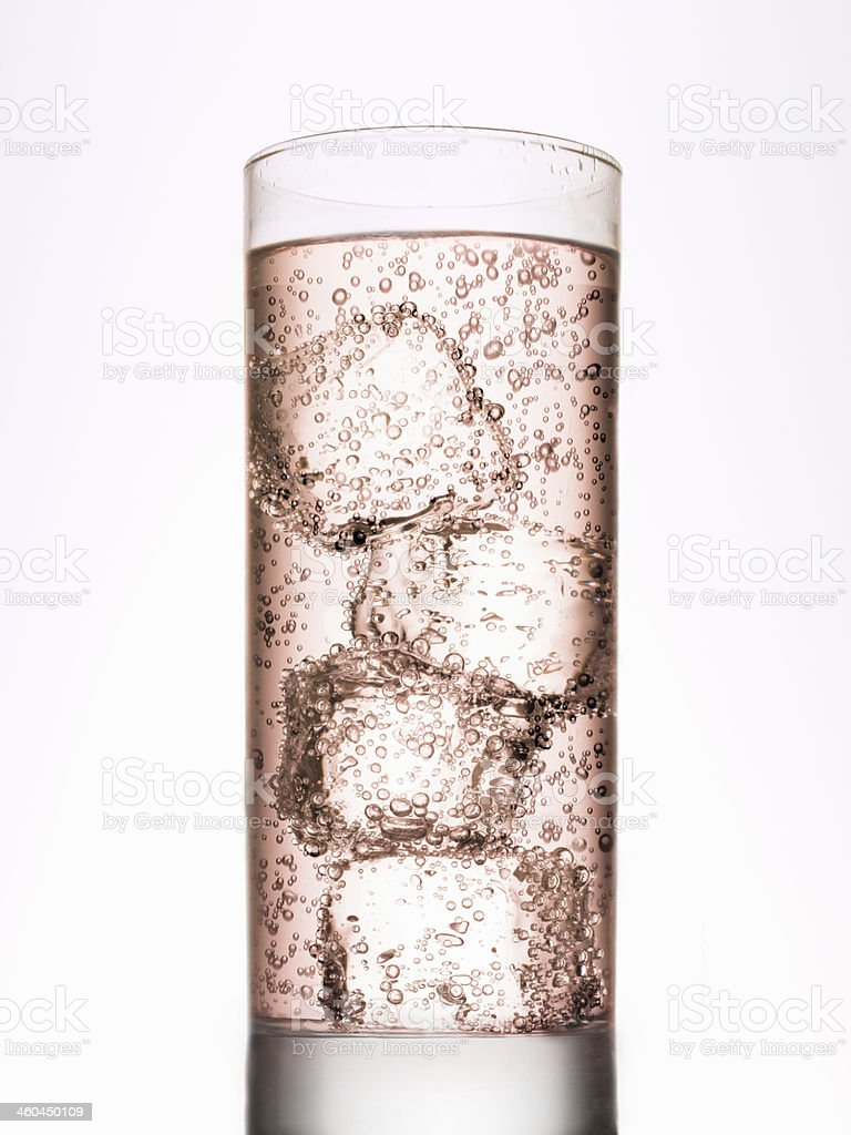 Brownish drink with ice cubes on white background royalty-free stock photo