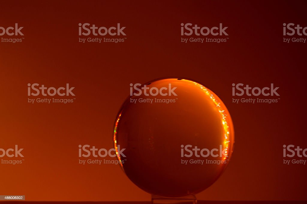 Brownish red orange sphere lit on sides.