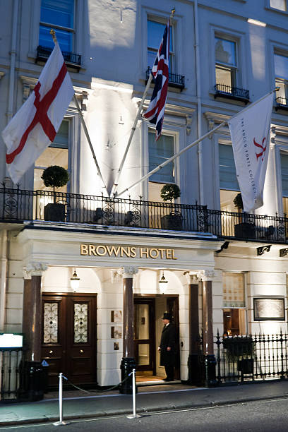 Browns Hotel - London London, England - February 7, 2011: The Browns Hotel at dusk. The doorman standing and waiting for guests. The Browns is a 5 star hotel located in Mayfair. mayfair stock pictures, royalty-free photos & images