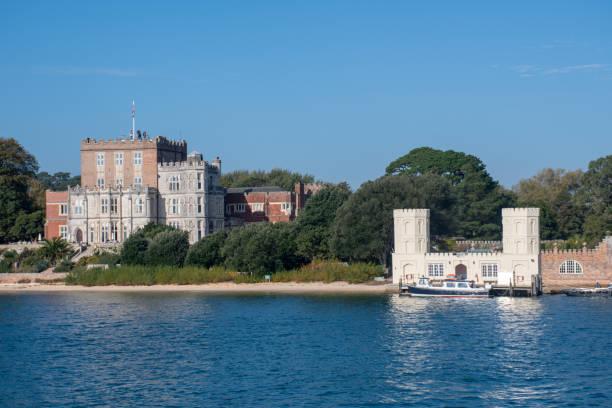 brownsea island castle used by john lewis partnership seen from boat in the harbour - john lewis стоковые фото и изображения