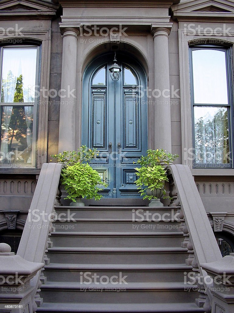 Brownstone entrance with tall wooden doors royalty-free stock photo