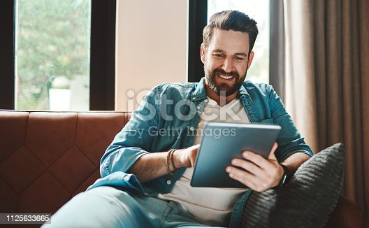 Cropped shot of a handsome young man using a tablet while chilling on the sofa at home