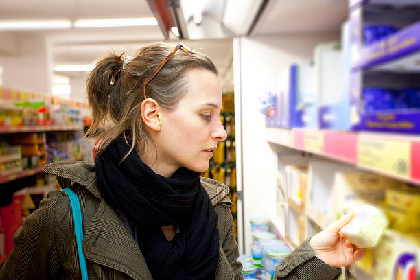 Browsing for Cheese in Supermarket Attractive Caucasian young woman is shopping in a supermarket for cheese. She is holding an item in her hand and is inspecting it.You might also like: discount store stock pictures, royalty-free photos & images