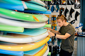 A shot of a young, Caucasian man browsing through surfboards in a surf board shop.