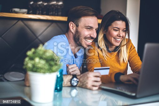 Young cheerful couple shopping online at home