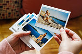 Young woman is browsing polaroid images from yesteryear summer vacation she spent with family in Greece. Authentic moments, original photographs.