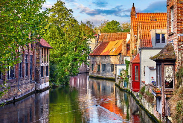 Bruges Belgium medieval ancient houses Bruges, Belgium. Medieval ancient houses made of old bricks at water channel with boats in old town. Summer sunset with sunshine and green trees. Picturesque landscape. belgium stock pictures, royalty-free photos & images