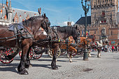 Bruges, Belgium - June 12, 2014: The Carriage on the Grote Markt and Belfort van Brugge in background with the tourists.