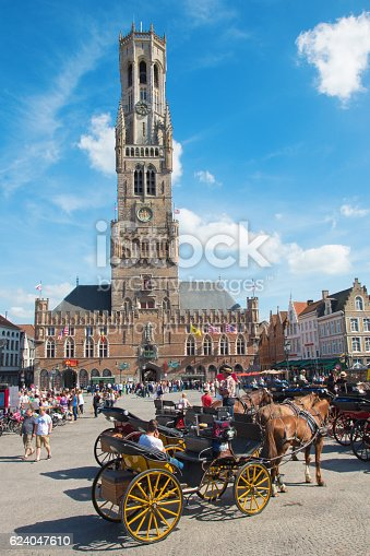 Bruges, Belgium - June 12, 2014: Bruges - The Carriage on the Grote Markt and Belfort van Brugge in background.