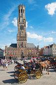 Bruges, Belgium - June 12, 2014: Bruges - The Carriage on the Grote Markt and Belfort van Brugge in background.