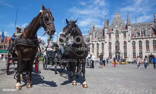 Bruges, Belgium - June 13, 2014: The Carriages on the Grote Markt in full tourist season and the Provinciaal Hof building in background.