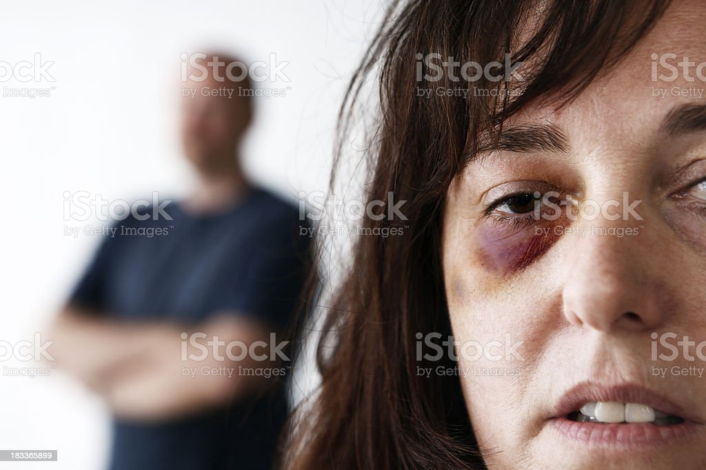 Bruised and battered woman with threatening male in background stock photo