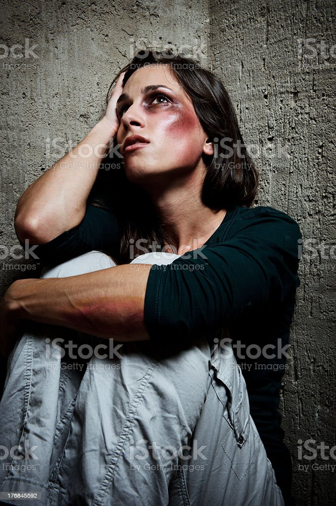 Bruised woman sitting on corner of concrete walls royalty-free stock photo