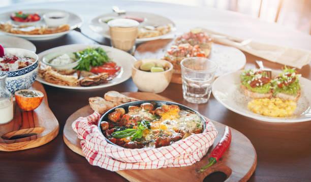 brunch mit verschiedenen gerichten-gebratene eier, crepes und tapas - sonntagsbrunch stock-fotos und bilder