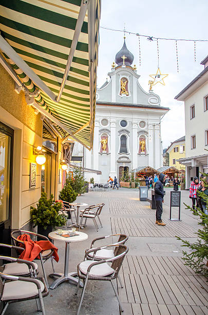 Brunico San Candido Brunico, Italy, 14 December 2014: A bistro chairs with the church of San Candido in the background during winter holidays bruneck stock pictures, royalty-free photos & images
