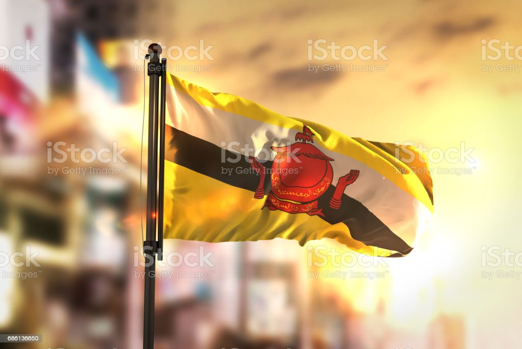 Brunei Flag Against City Blurred Background At Sunrise Backlight stock photo