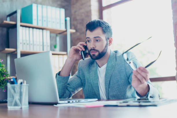 Brunet, attractive, young banker with bristle, in formal jacket talking on the smartphone, he is  annoyed, displeased, having conflict with client during telephone conversation, sitting at his desktop stock photo