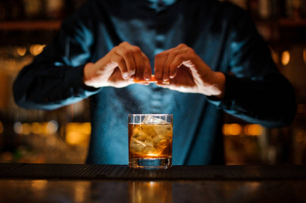 Brunet bartender adding a fresh orange citron to the cocktail picture id958940500?b=1&k=6&m=958940500&s=612x612&w=0&h=kwrtf73jvwm0rzdzkmzethl7bwrkibkyxmjszt3jk1w=