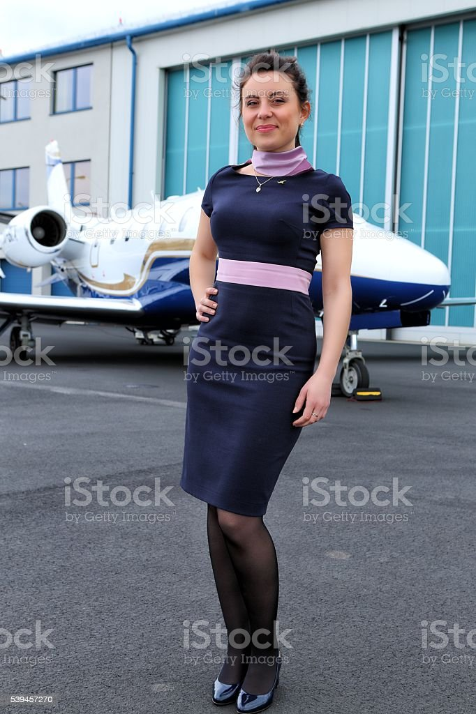 Brunette air hostess in front of business jet stock photo