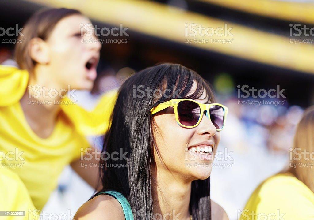 Brunette Brazilian beauty smiling at soccer match stock photo
