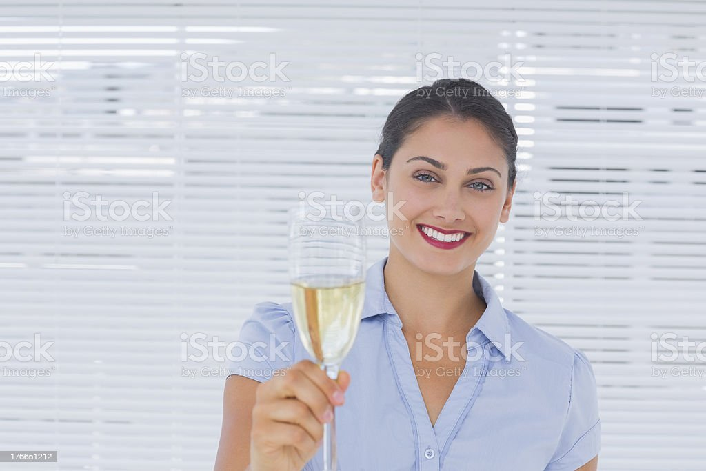 Brunette businesswoman raising a glass of champagne royalty-free stock photo