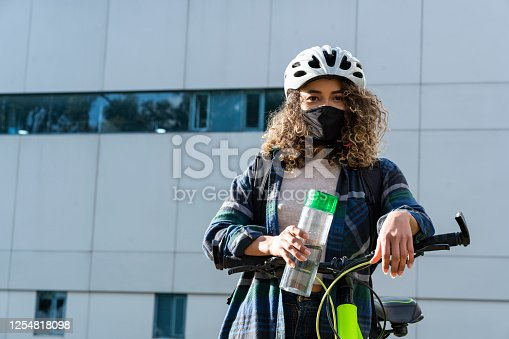 Average-age 25-year-old Latina woman dressed casually with dark-skinned curly afro hair wears her black face mask and rides a bike around town using it as her means of transportation.