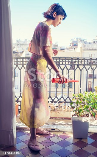 Brunette fashion woman watering flower pot in the balcony in Mediterranean city