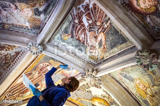Brunette Female Painter Restoring Ceiling Paintings with Paintbrush in Catholic Chapel - Stock Photo