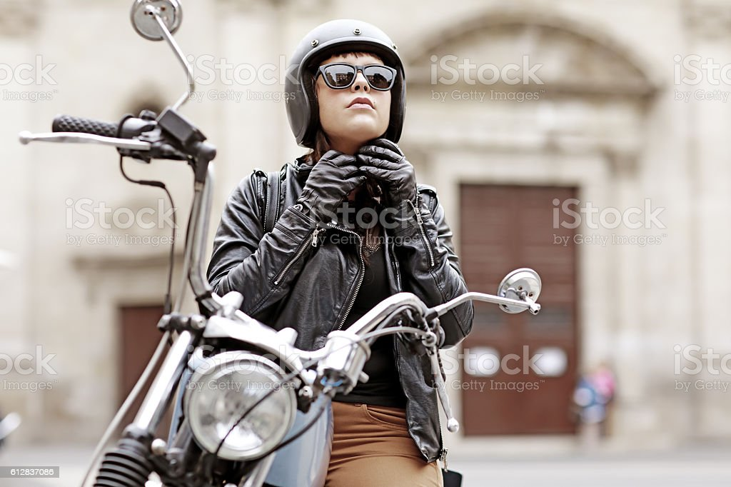 Brunette female posing on motorbike in old european city centre stock photo