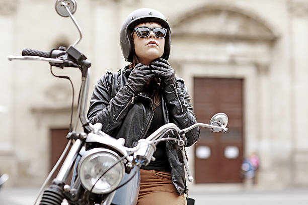 brunette female posing on motorbike in old european city centre - biker stock photos and pictures