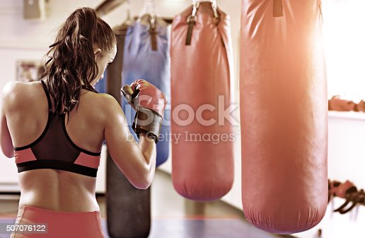 497607484 istock photo Brunette female posing out at a boxing gym 507076122