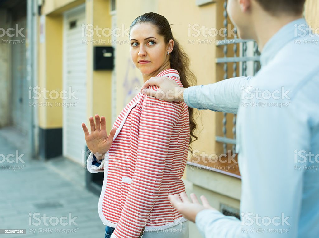 brunette girl asking man to stop bothering her outdoors stock photo