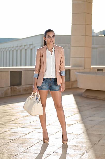 brunette mädchen gekleidet mit blazer - handtasche jeans stock-fotos und bilder